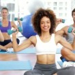 Fitness class sitting in lotus pose together lifting dumbbells — Stock Video