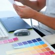 Graphic designer looking at colour samples at his desk — Stock Video