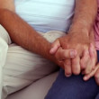 Senior couple holding hands on the couch — Stock Video #42664917