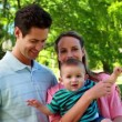 Couple holding their baby son in the park — Vídeo de Stock