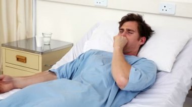 Sick man lying on hospital bed coughing — Stok video