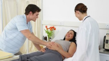 Brunette pregnant woman lying on bed talking with partner and doctor — Stock Video