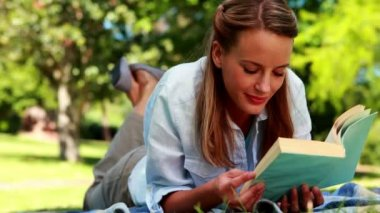 Pretty blonde reading a book lying on a blanket in the park — Stock Video
