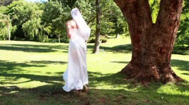 Excited bride holding a bouquet in the park — Stock Video