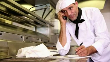 Handsome chef writing on clipboard while talking on phone — Stock Video