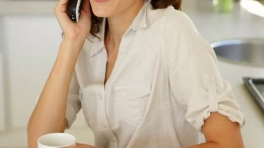 Pretty woman drinking coffee and chatting on phone — Stock Video
