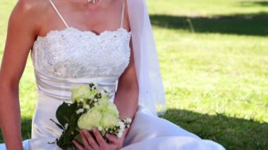 Smiling bride sitting on the grass — Vidéo
