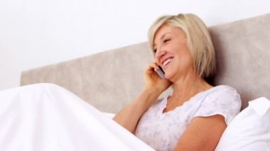 Happy woman talking on phone in bed — Vidéo