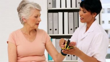 Nurse showing elderly patient how to put on wrist brace — Stock Video