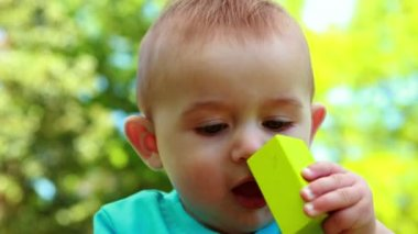 Adorable baby boy chewing building blocks — Stock Video