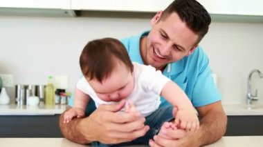 Cheerful father playing with his baby boy — Stock Video