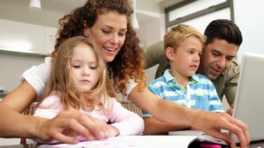 Ъchildren drawing at the table with their parents and using laptop — ストックビデオ