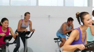 Spinning class in fitness studio led by energetic instructor — Stock Video