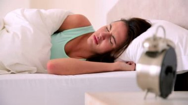 Sleepy brunette knocking her alarm clock off — Stock Video