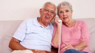 Senior couple sitting on sofa talking on the phone — Stock Video