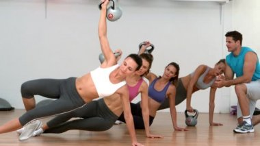 Fitness class lifting kettle bells together in side plank — Stock Video