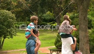 Parents giving their children piggyback ride — Stock Video