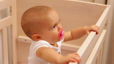 Cute baby girl standing in her cot — Stock Video