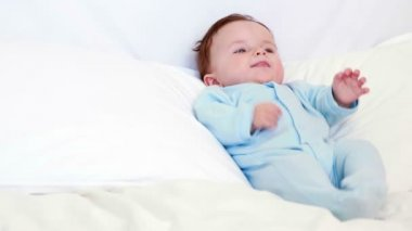 Baby boy in blue babygro lying on pillows — Stockvideo
