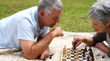 Senior couple relaxing in the park lying on a blanket playing chess — Stock Video