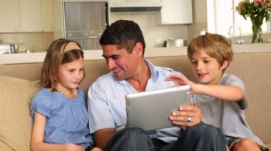 Cute children using tablet with father on couch — Stock Video