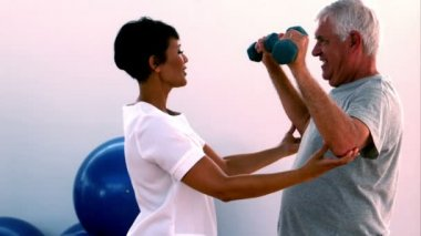 Elderly man lifting hand weights with physiotherapist — Stock Video