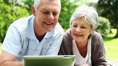 Happy senior couple relaxing in the park using tablet — Stock Video