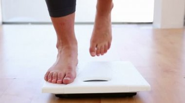Woman stepping on scales — Stok video