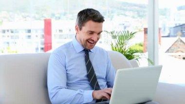 Businessman typing on laptop sitting on sofa — Stock Video