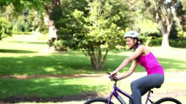 Fit girl going for a bike ride in the park — Stock Video