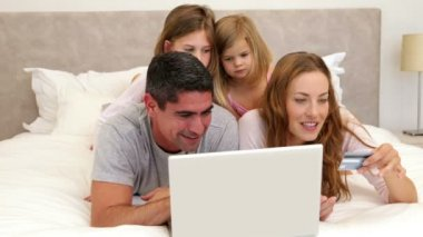 Parents and daughters lying on bed shopping online with laptop — Stock Video