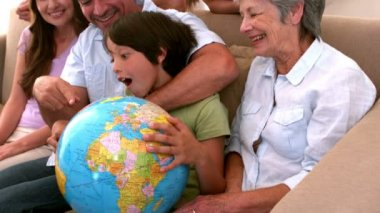 Extended family looking at globe together on couch — Stock Video