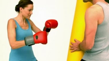 Fit woman punching a bag held by trainer — Stock Video