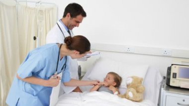 Sick little girl lying in bed talking to nurse and doctor — Stock Video