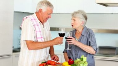 Senior couple preparing a healthy meal while drinking red wine — Stock Video