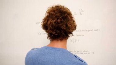 Confused student standing in front of whiteboard of math — 图库视频影像