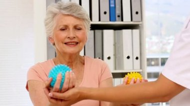 Nurse showing elderly patient how to use massage balls — Stock Video