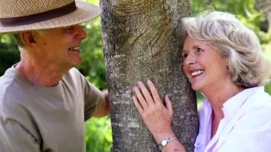 Retired couple leaning against tree smiling at each other — Stock Video