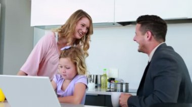 Mother and father laughing together while daughter uses laptop — Stock Video