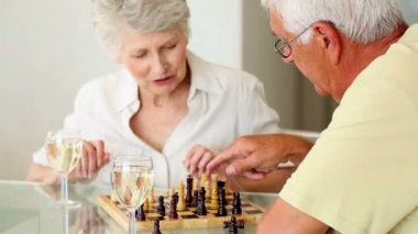 Senior couple sitting at table playing chess — Stock Video