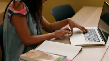 Pretty student studying at desk in classroom — Vídeo de Stock