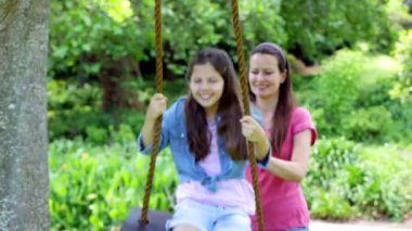 Mother pushing her daughter on a swing — Stock Video