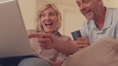 Couple shopping online on the couch — Vídeo de stock
