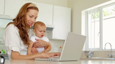 Beautiful brunette using laptop and holding her baby daughter — Stock Video