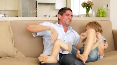 Father and daughter tickling little boy in the couch — Stock Video