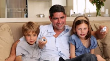 Cute children playing video games with their father on the sofa — Stock Video