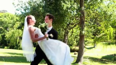 Groom picking up his pretty new wife in the park — Stock Video