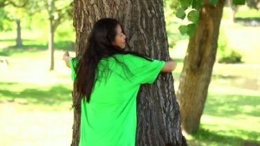Happy environmental activist hugging a tree — Stock Video