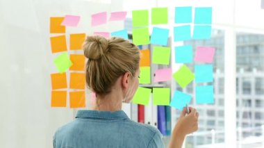 Blonde designer looking at post its on window — Stock Video