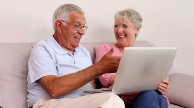 Senior couple sitting on sofa using laptop — Stock Video